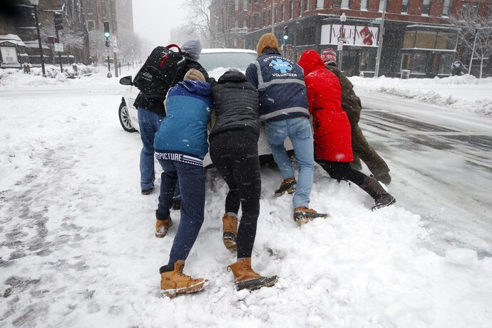 People push a stranded taxi during a snowstorm, Tuesday, March 13, 2018, in Boston.  The third major nor'easter in two weeks slammed New England on Tuesday, bringing blizzard conditions and more than a foot of snow to some communities.   (AP Photo/Michael Dwyer)