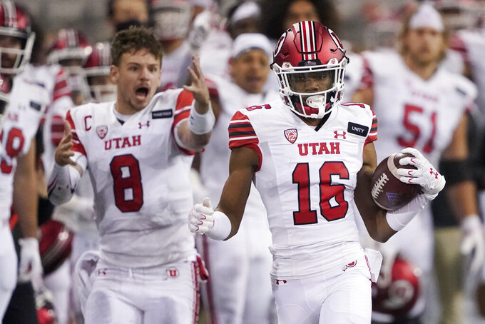 Utah safety Zemaiah Vaughn (16) runs 73 yards as quarterback Jake Bentley (8) reacts on the sideline after Vaughn intercepted a Washington pass during the first half of an NCAA college football game Saturday, Nov. 28, 2020, in Seattle. (AP Photo/Ted S. Warren)