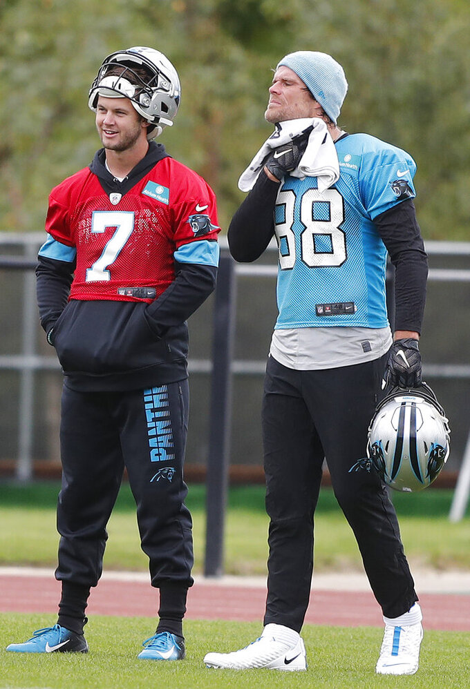 Panthers QB Kyle Allen, left, and Greg Olsen pause during a NFL training session of the Carolina Panthers at Harrow School in London, Friday, Oct. 11, 2019. The Carolina Panthers are preparing for an NFL regular season game against the Tampa Bay Buccaneers in London on Sunday. (AP Photo/Frank Augstein)