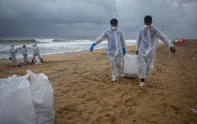 Sri Lankan navy soldiers carry sacks full of plastic debris washed ashore from fire damaged container ship MV X-Press Pearl at Kapungoda, on the outskirts of Colombo, Sri Lanka. Monday, June 14, 2021. (AP Photo/Eranga Jayawardena)