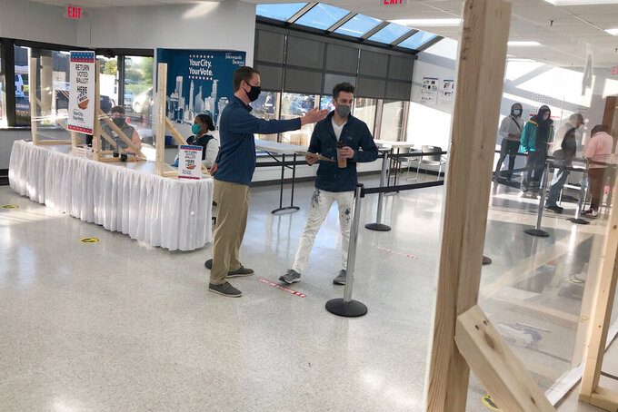 An election official directs Jason Miller of Minneapolis to the check-in desk at the city's early voting center on Friday, Sept. 18, 2020. Miller was the first in line at the center in Minneapolis as early voting opened in Minnesota. (AP Photo/Steve Karnowski)