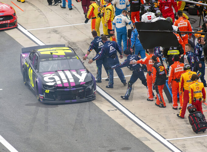 Jimmie Johnson's team puts out their hands as he leaves pit road for the start of the Drydene 400 - Monster Energy NASCAR Cup Series playoff auto race, Sunday, Oct. 6, 2019, at Dover International Speedway in Dover, Del. (AP Photo/Jason Minto)