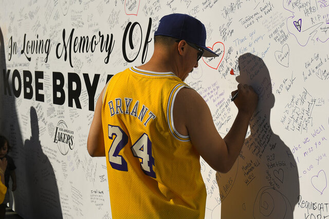 A fan signs a remembrance board in front of Staples Center where the Los Angeles Lakers play to memorialize Kobe Bryant Tuesday, Jan. 28, 2020, in Los Angeles following a helicopter crash that killed former NBA basketball player and his 13-year-old daughter, Gianna, and seven others. (AP Photo/Mark J. Terrill)