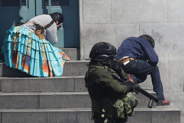 Pedestrians take cover from tear gas launched by security forces at anti-government demonstrators in La Paz, Bolivia, Thursday, Nov. 21, 2019. Backers of former President Evo Morales have taken to the streets asking for his return since he resigned on Nov. 10 under pressure from the military after weeks of protests against him over a disputed election he claim to have won. (AP Photo/Natacha Pisarenko)