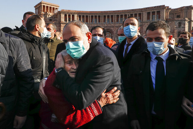 Armenian Prime Minister Nikol Pashinyan comforts a woman during a march of remembrance of the heroes killed in a war over the Nagorno-Karabakh region, in Yerevan, Armenia, Saturday, Dec. 19, 2020. Both opponents and supporters of Armenia's prime minister rallied Saturday as the nation paid tribute to the thousands who died in fighting with Azerbaijan over the region of Nagorno-Karabakh. Critics demanded that the leader resign and tried to pelt him with eggs. (Tigran Mehrabyan/PAN Photo via AP)