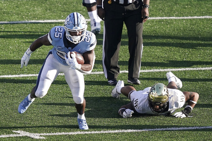 North Carolina running back Javonte Williams (25) finds some running room during the second half of an NCAA college football game against Wake Forest in Chapel Hill, N.C., Saturday, Nov. 14, 2020. (AP Photo/Gerry Broome)