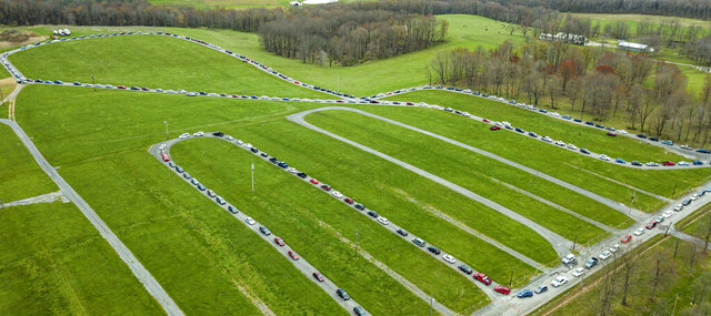 Hundreds of cars wait in line for a food bank distribution at the Big Butler Fairgrounds on Tuesday, April 28, 2020, in Prospect, Pa. The Greater Pittsburgh Community Food Bank expected more than 1,500 vehicles to come to receive two 25-pound boxes of food each. (Andrew Rush/Pittsburgh Post-Gazette via AP)