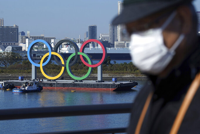 FILE - In this Tuesday, Dec. 1, 2020 file photo, a man wearing a protective face mask to help curb the spread of the coronavirus walks with the Olympic rings in the background in the Odaiba section, in Tokyo. The United States, Russia and China were each given an extra entry to the Olympic women's gymnastics competition in Tokyo on Wednesday, Feb. 10, 2021, after the coronavirus pandemic forced a shake-up in qualifying. (AP Photo/Eugene Hoshiko, File)