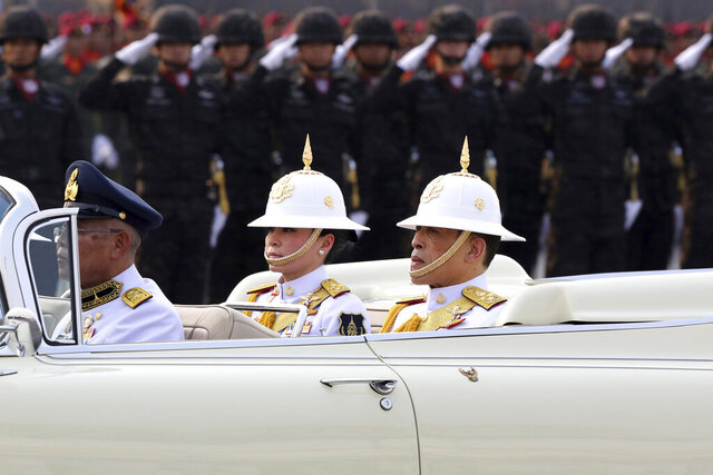 Thailand's King Maha Vajiralongkorn, right and Queen Suthida, review the royal guard during Armed Forces Day  at Adisorn military camp's Cavalry Centre at Saraburi province central Thailand, Saturday, Jan. 18, 2020. Thailand's king has presided over an oath-taking ceremony at an army base where almost 7,000 soldiers and police paraded to mark Armed Forces Day. The king's presence at Saturday's ceremony was unusual,  as Thai monarchs have rarely, if ever, attended the occasion, even though the royal palace and the military are closely linked. (AP Photo/Thanis Sudto)