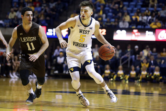 West Virginia guard Jordan McCabe (5) drives upcourt while defended by Lehigh guard Jordan Cohen (11) during the second half of an NCAA college basketball game Sunday, Dec. 30, 2018, in Morgantown, W.Va. (AP Photo/Raymond Thompson)