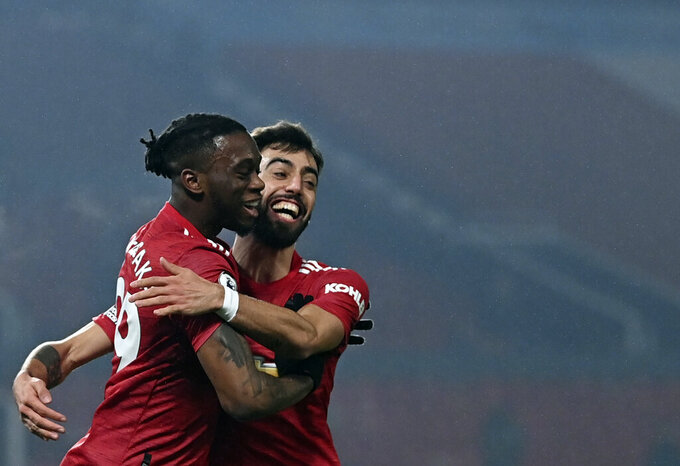 Manchester United's Aaron Wan-Bissaka, left, celebrates with Manchester United's Bruno Fernandes after scoring his side's opening goal during the English Premier League soccer match between Manchester United and Southampton, at the Old Trafford stadium in Manchester, England, Tuesday, Feb. 2, 2021.(Laurence Griffiths/Pool via AP)