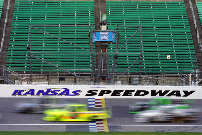 Drivers take the green flag at the start of a NASCAR Truck Series auto race at Kansas Speedway in Kansas City, Kan., Friday, July 24, 2020. (AP Photo/Charlie Riedel)