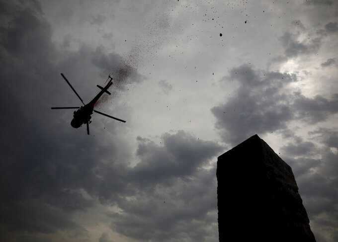 An Indian Air Force helicopter showers flower petals at the National Police Memorial in New Delhi, India, Sunday, May 3, 2020. The event was part the Armed Forces' efforts to thank the workers, including doctors, nurses and police personnel, who have been at the forefront of the country's battle against the COVID-19 pandemic. (AP Photo/Manish Swarup)
