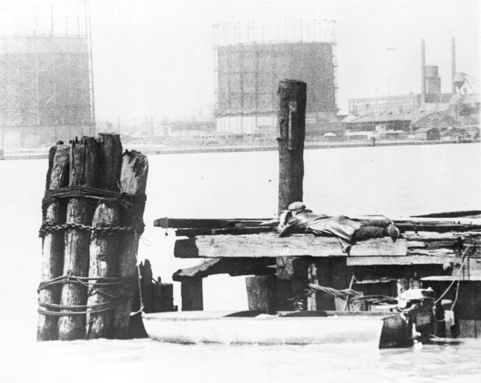 FILE - In this April 28, 1929, file photo a rum runner in Windsor, on the Canadian side of the Detroit River, watches with field glasses for lookout on the American side to signal that no prohibition agents are in sight. His outboard motorboat, loaded with illegal liquor, is shown beneath pilings. (AP Photo, File)