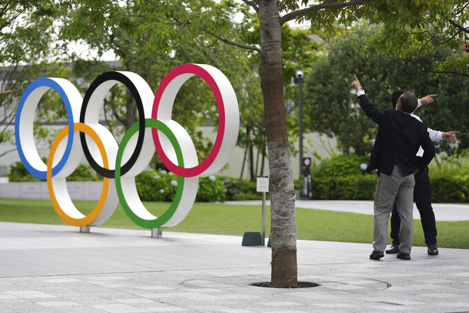 Men gesture near the Olympic Rings Wednesday, June 2, 2021, in Tokyo. (AP Photo/Eugene Hoshiko)