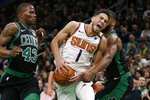 Phoenix Suns guard Devin Booker (1) yells as he drives to the basket between Boston Celtics guard Javonte Green (43) guard Brad Wanamaker (9) during the first half of an NBA basketball game, Saturday, Jan. 18, 2020, in Boston. (AP Photo/Mary Schwalm)
