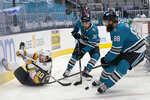 Vegas Golden Knights center Chandler Stephenson, left, reaches behind for the puck next to San Jose Sharks defensemen Mario Ferraro (38) and Brent Burns (88) during the second period of an NHL hockey game in San Jose, Calif., Wednesday, May 12, 2021. (AP Photo/Jeff Chiu)
