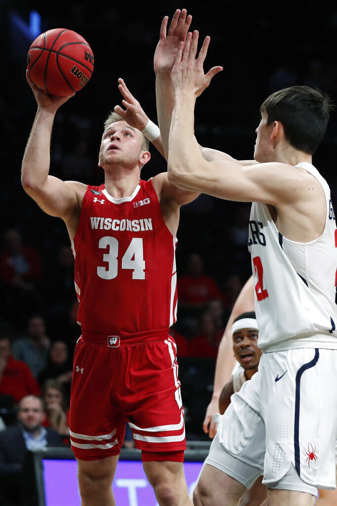 Wisconsin guard Brad Davison (34) takes a shot with Richmond guard Andre Gustavson (22) defending during the first half of an NCAA college basketball game in the Legends Classic, Monday, Nov. 25, 2019, in New York. (AP Photo/Kathy Willens)