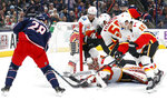 Calgary Flames' David Rittich, bottom center, of the Czech Republic, makes a save against Columbus Blue Jackets' Oliver Bjorkstrand, left, of Denmark, during the second period of an NHL hockey game Saturday, Nov. 2, 2019, in Columbus, Ohio. (AP Photo/Jay LaPrete)