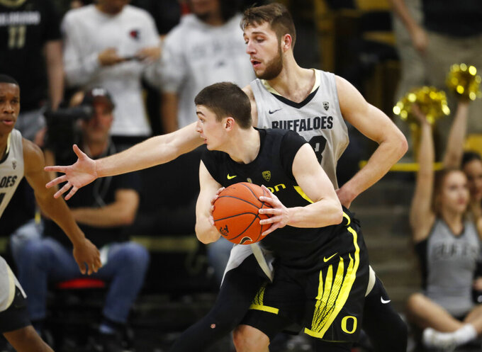 Oregon guard Payton Pritchard, front, looks to pass the ball as Colorado forward Lucas Siewert defends during the second half of an NCAA basketball game Saturday, Feb. 2, 2019, in Boulder, Colo. Colorado won 73-51. (AP Photo/David Zalubowski)