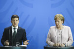 German Chancellor Angela Merkel, right, and Ukrainian President Volodymyr Zelenskiy, left, attend a joint news conference after a meeting at the chancellery in Berlin, Germany, Tuesday, June 18, 2019. (AP Photo/Markus Schreiber)