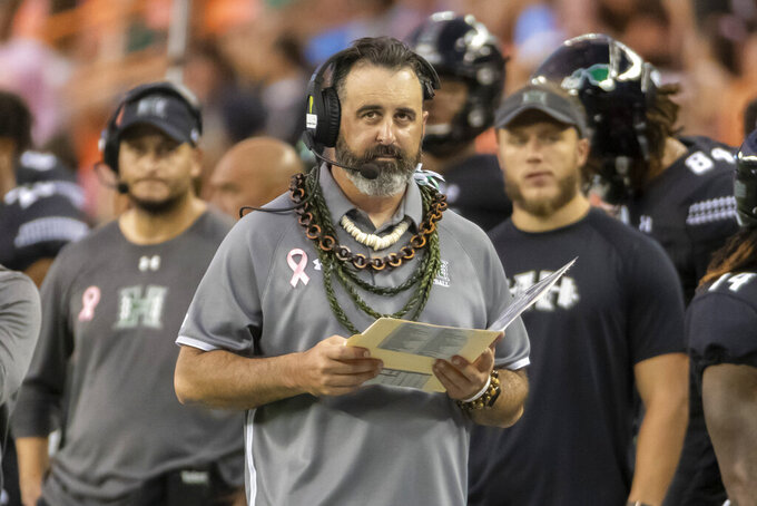 Hawaii head coach Nick Rolovich glances up at the scoreboard during the first half of an NCAA college football game against Air Force, Saturday, Oct. 19, 2019, in Honolulu. (AP Photo/Eugene Tanner)