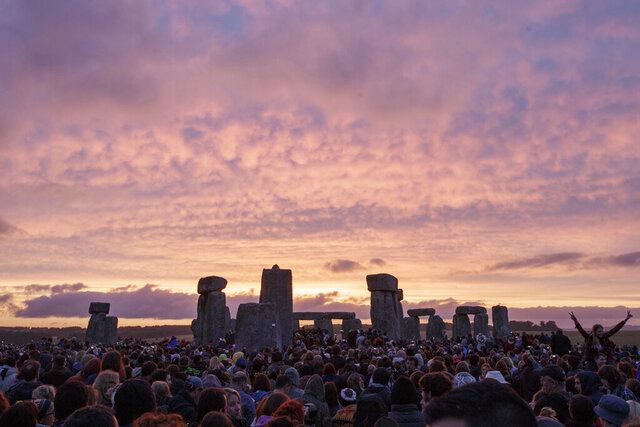 FILE - In this Sunday, June 21, 2015 file photo, the sun rises as thousands of revellers gather at the ancient stone circle Stonehenge to celebrate the Summer Solstice, the longest day of the year, near Salisbury, England. Archaeologists said Monday June 22, 2020, they have discovered a major new prehistoric monument under the earth near Stonehenge that could shed new light on the origins of the mystic stone circle that is the subject of continued scientific research and venue for modern day pagan celebrations. (AP Photo/Tim Ireland, File)
