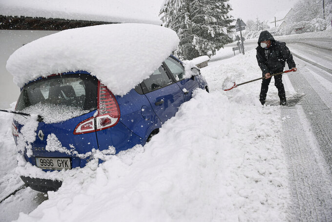 CORRECTING DATE TO SUNDAY - A man clears the snow from a road close to his car as the snow falls in the small village of Espinal, northern Spain, Sunday, Dec. 6, 2020. (AP Photo/Alvaro Barrientos)