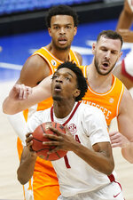 Alabama's Herbert Jones (1) drives past Tennessee defenders in the first half of an NCAA college basketball game in the Southeastern Conference Tournament Saturday, March 13, 2021, in Nashville, Tenn. (AP Photo/Mark Humphrey)