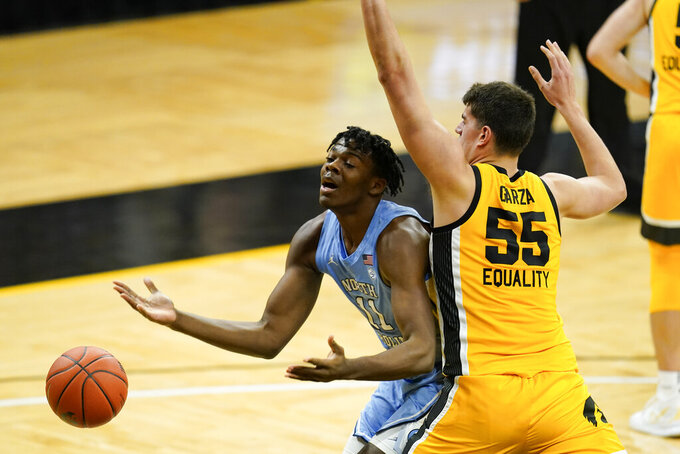 North Carolina forward Day'Ron Sharpe, left, loses the ball while driving past Iowa center Luka Garza, right, during the first half of an NCAA college basketball game, Tuesday, Dec. 8, 2020, in Iowa City, Iowa. (AP Photo/Charlie Neibergall)