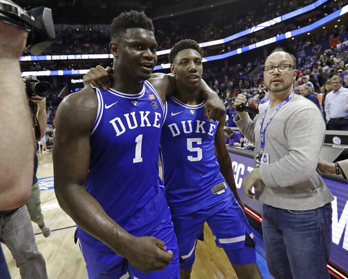 Duke's Zion Williamson (1) and RJ Barrett (5) embrace as they leave the court after Duke defeated North Carolina in an NCAA college basketball game in the Atlantic Coast Conference tournament in Charlotte, N.C., Friday, March 15, 2019. (AP Photo/Chuck Burton)
