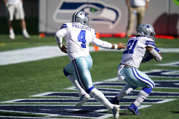 Dallas Cowboys quarterback Dak Prescott (4) hands off to running back Ezekiel Elliott (21) during the first half of an NFL football game against the Seattle Seahawks, Sunday, Sept. 27, 2020, in Seattle. Elliott was tackled in the end zone for a safety on the play. (AP Photo/Elaine Thompson)