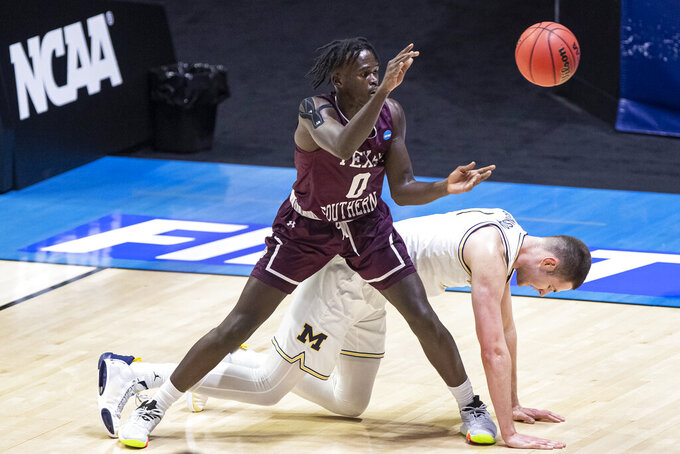 Texas Southern's Yahuza Rasas (0) grabs a pass next to Michigan's Hunter Dickinson during the second half of a first-round game in the NCAA men's college basketball tournament, Saturday, March 20, 2021, at Mackey Arena in West Lafayette, Ind.  (AP Photo/Robert Franklin)