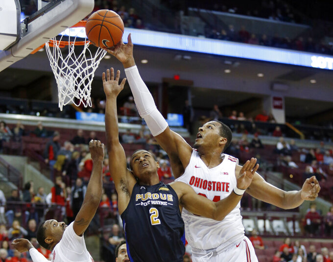 Ohio State forward Kaleb Wesson, right, blocks a shot by Purdue Fort Wayne guard Brian Patrick (2) as Ohio State guard Luther Muhammad defends during the first half of an NCAA college basketball game in Columbus, Ohio, Friday, Nov. 22, 2019. (AP Photo/Paul Vernon)