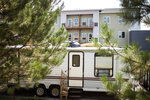 A RV is parked on Sacco Drive next to an affordable housing development under construction on Friday, July 30, 2021, in Bozeman, Mont. Small cities of all varieties of motor homes have popped up in local campgrounds, big-box store parking lots and side streets.(Rachel Leathe/Bozeman Daily Chronicle via AP)