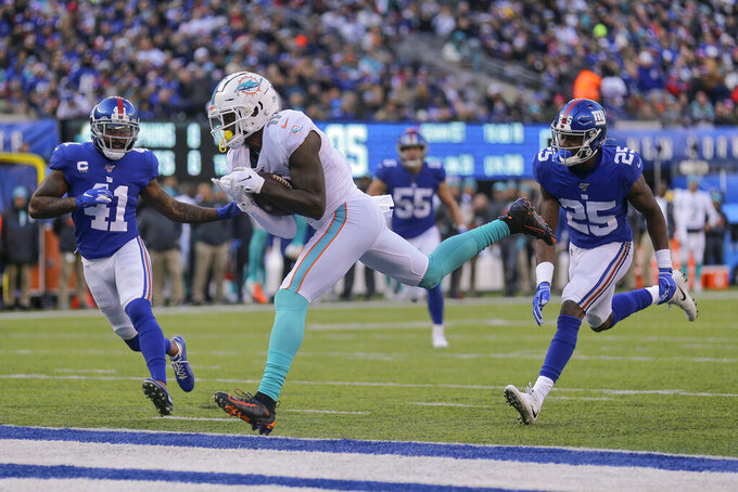 Miami Dolphins wide receiver DeVante Parker (11) comes down with a pass to score a touchdown against New York Giants free safety Antoine Bethea (41) and defensive back Corey Ballentine (25) during the second quarter of an NFL football game, Sunday, Dec. 15, 2019, in East Rutherford, N.J. (AP Photo/Seth Wenig)