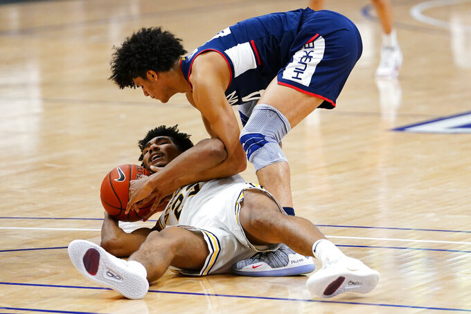 Villanova's Jermaine Samuels, bottom, and Connecticut's Andre Jackson battle for a loose ball during the second half of an NCAA college basketball game, Saturday, Feb. 20, 2021, in Villanova, Pa. (AP Photo/Matt Slocum)