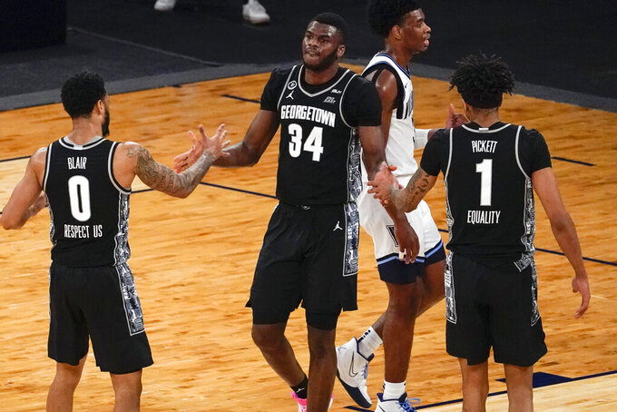 Georgetown center Qudus Wahab (34), guard Jahvon Blair (0) and forward Jamorko Pickett (1) celebrate after Wahab scored during the second half of an NCAA college basketball game against Villanova in the quarterfinals of the Big East conference tournament, Thursday, March 11, 2021, in New York. Georgetown won 72-71. (AP Photo/Mary Altaffer)