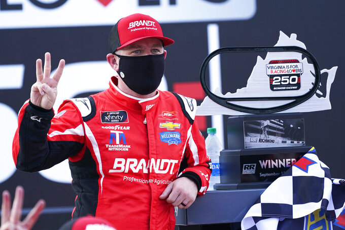 Justin Allgaier poses with his trophy in Victory Lane as he celebrates after winning a NASCAR Xfinity Series auto race Saturday, Sept. 12, 2020, in Richmond, Va. Allgaier swept the two days of racing in the Xfinity Series. (AP Photo/Steve Helber)