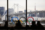 People dine in a hotel restaurant as the Olympic Rings float in the water near the Rainbow Bridge Friday, Jan. 17, 2020, in Tokyo. (AP Photo/Jae C. Hong)
