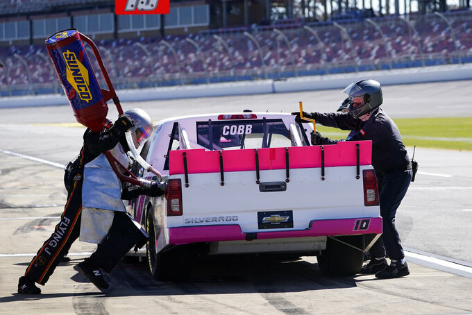 Pit crew members work to fuel and make adjustments to Jennifer Cobb's truck during the NASCAR Truck series auto race at Talladega Superspeedway Saturday, Oct. 3, 2020, in Talladega, Ala. (AP Photo/John Bazemore)