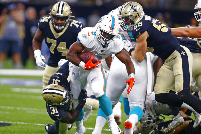 Miami Dolphins running back Mark Walton (9) carries as New Orleans Saints defensive back Chris Banjo (31) tries to tackle in the first half of an NFL preseason football game in New Orleans, Thursday, Aug. 29, 2019. (AP Photo/Butch Dill)