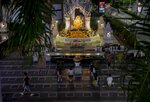 Devotees pray as they stay inside marked areas for social distancing at a shrine for Hindu god Ganesh, outside a shopping mall in Bangkok, Thailand, Tuesday, Dec. 29, 2020. Thailand reported more than 155 new coronavirus infections and its first fatality since November on Tuesday as the virus spread from two recently identified clusters to other parts of the country. (AP Photo/Gemunu Amarasinghe)