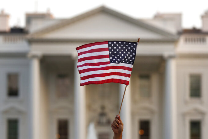 FILE - In this Sept. 5, 2017, file photo, a flag is waved outside the White House, in Washington. The Trump administration is extending a ban on green cards issued outside the United States until the end of 202 and adding many temporary work visas to the freeze, including those used heavily by technology companies and multinational corporations. (AP Photo/Carolyn Kaster, File)