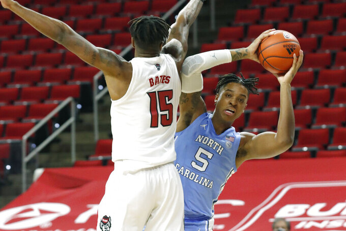 North Carolina's Armando Bacot (5) looks for room as N.C. State's Manny Bates (15) defends during the first half of an NCAA college basketball game against North Carolina in Raleigh, N.C., Tuesday, Dec. 22, 2020.(Ethan Hyman/The News & Observer via AP)
