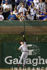 A fan catches a home run by Chicago Cubs' Willson Contreras as Cincinnati Reds' Josh VanMeter leaps for the ball during the seventh inning of a baseball game Wednesday, Sept. 18, 2019, in Chicago. (AP Photo/Charles Rex Arbogast)