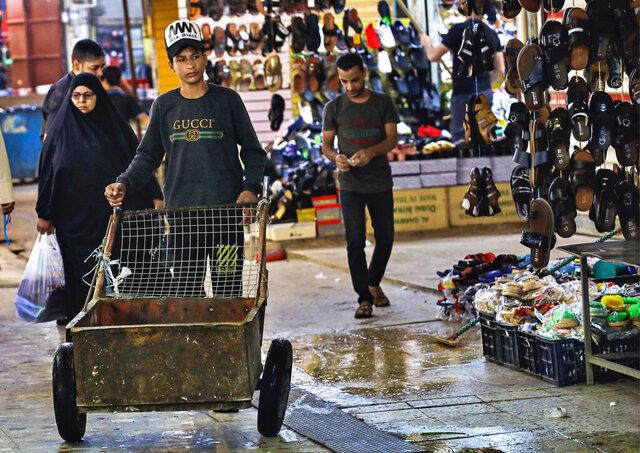 FILE - In this Oct. 21, 2020 file photo, people shop at old Basra market, Iraq.  A leaked draft of Iraq's state budget has spurred panic as it confirmed the government's intentions to devalue the national currency, the Iraqi dinar, and cut salaries to cope with a severe economic crisis. Multiple officials confirmed the authenticity of the 2021 draft budget law that was making the rounds on social media on Thursday, Dec. 17.  (AP Photo/Nabil al-Jurani, File)