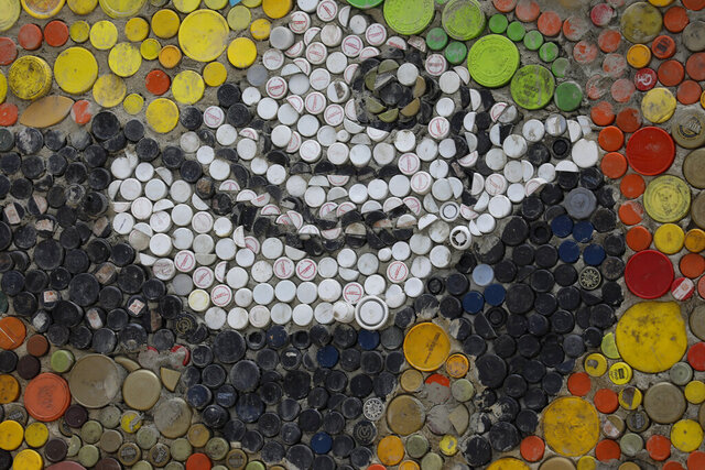 Plastic bottle caps form the face of a macaw within a large mosaic by Venezuelan artist Oscar Olivares in El Hatillo on the outskirts of Caracas, Venezuela, Thursday, Jan. 30, 2020. Olivares, 23, is using thousands of plastic bottle caps to create this mural. (AP Photo/Ariana Cubillos)