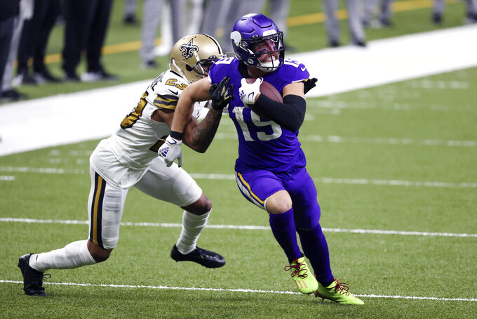 Minnesota Vikings wide receiver Adam Thielen (19) carries on a pass reception against New Orleans Saints cornerback Marshon Lattimore (23) in the first half of an NFL football game in New Orleans, Friday, Dec. 25, 2020. (AP Photo/Butch Dill)