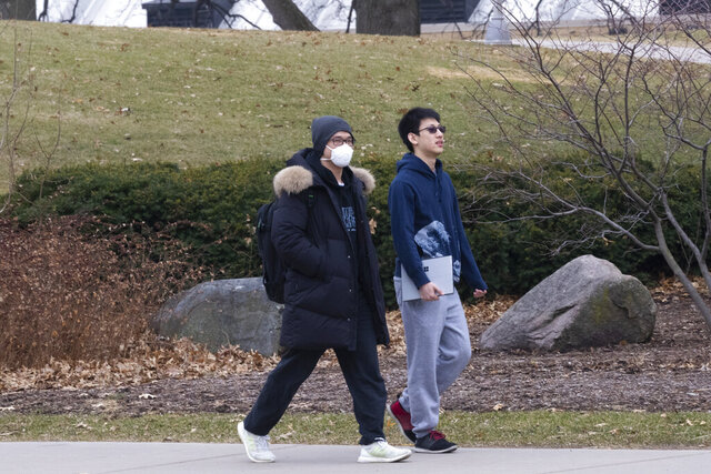 A masked pedestrian walks near Camp Randall Stadium Thursday, March 12, 2020 on the campus of UW-Madison in Madison, Wis. The university is one of multiple Wisconsin universities on Wednesday took dramatic steps to ward off or curb the spread of the COVID-19 outbreak, everything from moving courses online to canceling university-sponsored travel and events to extending spring break. (Mark Hoffman/Milwaukee Journal-Sentinel via AP)